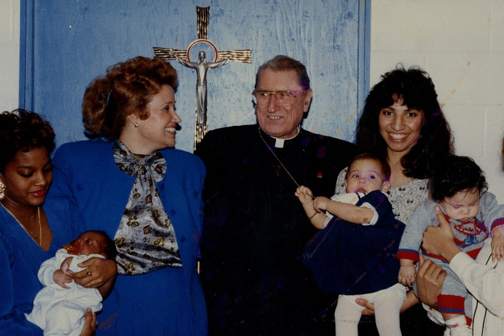 Kathy with mother and babies standing with Cardinal O'connor
